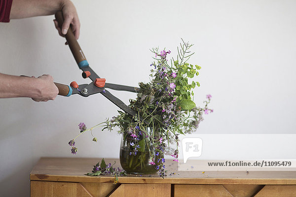 Frustrated woman cutting vase flower with secateurs