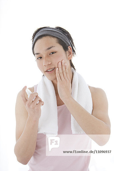 Young Man with Headband Using Skincare Product