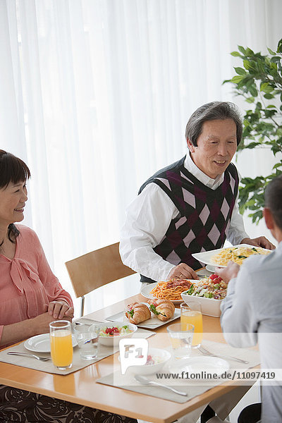 Three Mature People Having Lunch