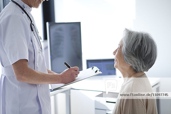 Doctor Taking Notes From Senior Female Patient