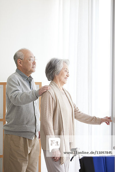 Senior Couple Looking Through Window