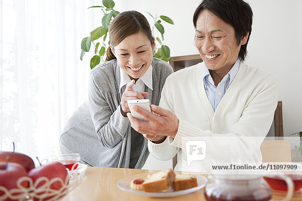 Couple Looking at Smart Phone Over Tea