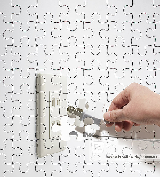 Puzzle of hand with electric plug