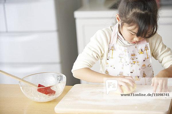 Girl kneading bread dough