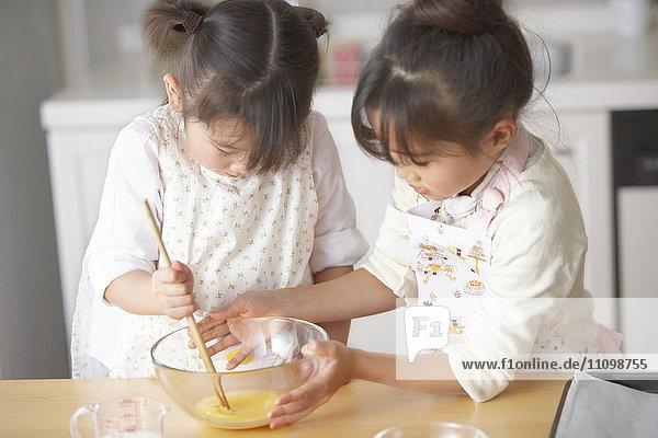 Girls beating egg
