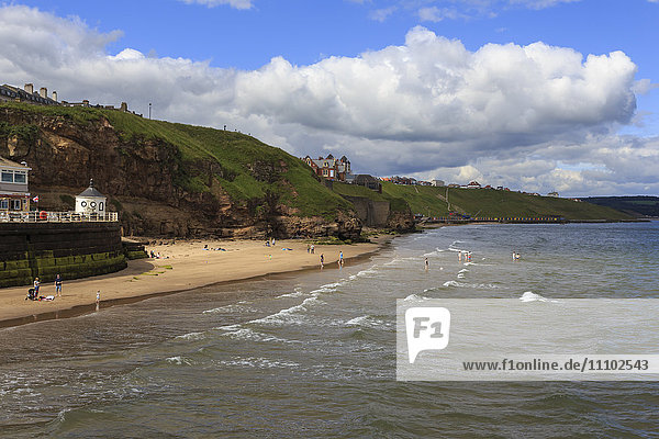 Bathers on West Cliff Beach  backed by grassy cliffs in summer  Whitby  North Yorkshire  England  United Kingdom  Europe