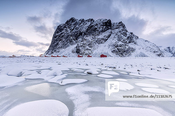 Snowy peaks and ice frame the typical fishermen houses called Rorbu  Eggum  Vestvagoy (Vest-Vagoy) Island  Lofoten Islands  Arctic  Norway  Scandinavia  Europe