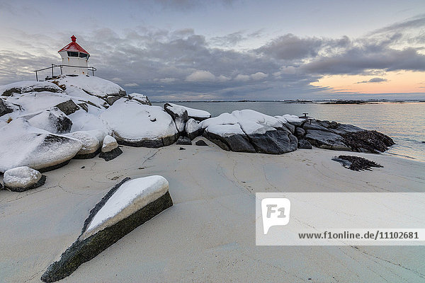 Colorful arctic sunset on the lighthouse surrounded by snow and icy sand  Eggum  Vestvagoy (Vest-Vagoy) Island  Lofoten Islands  Arctic  Norway  Scandinavia  Europe