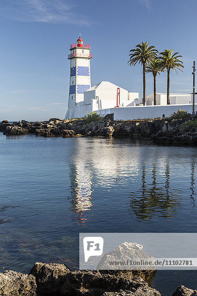 The lighthouse reflected in the blue water under the blue summer sky  Cascais  Estoril Coast  Lisbon  Portugal  Europe