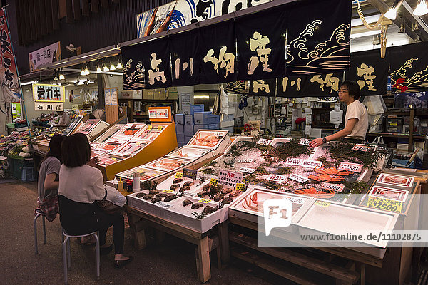 Diners sit and talk to seafood stall owner  Omicho fresh food market  network of covered stall lined streets  Kanazawa  Japan  Asia