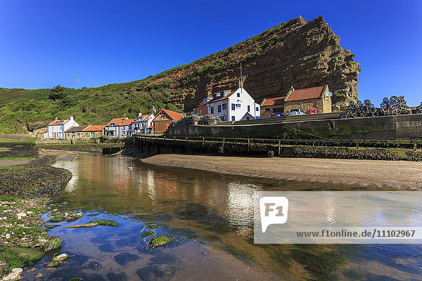 Harbour cottages beneath steep cliffs  fishing village  low tide in summer  Staithes  North Yorkshire Moors National Park  Yorkshire  England  United Kingdom  Europe