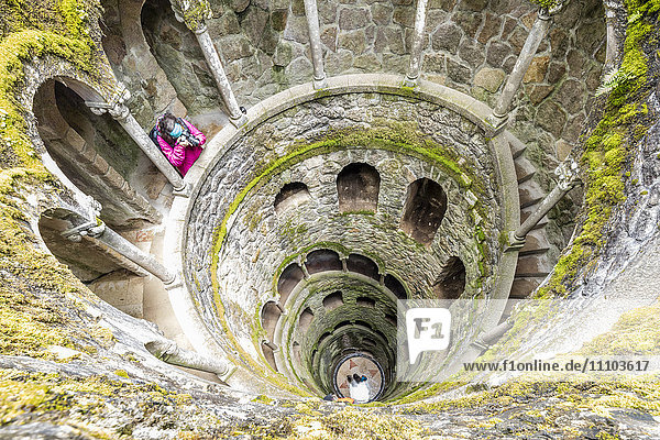 Photographer at the top of the spiral stairs inside the towers of Initiation Well at Quinta da Regaleira  Sintra  Portugal  Europe