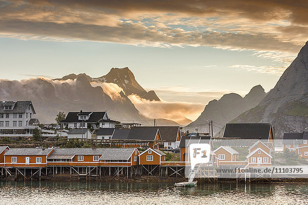 Sunset on the fishing village framed by rocky peaks and sea  Sakrisoya  Nordland county  Lofoten Islands  Arctic  Northern Norway  Scandinavia  Europe