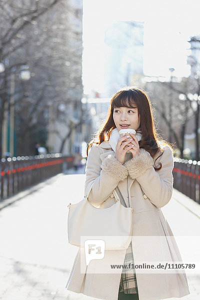 Attractive young Japanese woman with coffee outside
