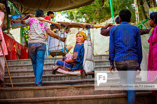Woman carried in a hanging chair to the temple  Holi Festival  Vrindavan  Uttar Pradesh  India  Asia
