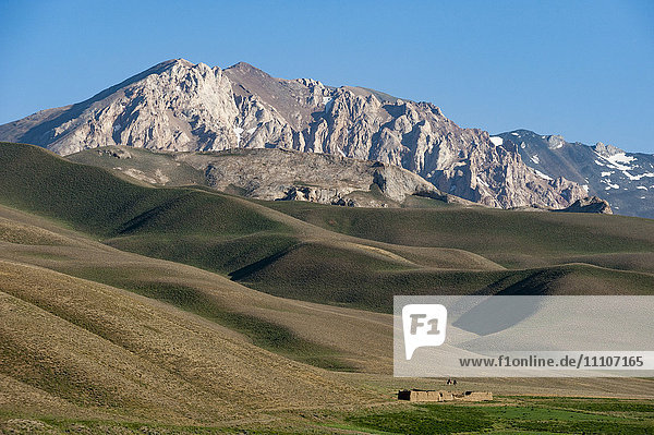 A distant house in the grasslands with views of mountains in the distance  Bamiyan province  Afghanistan  Asia