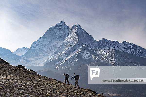 Trekkers climb a small peak above Dingboche in the Everest region in time to see the sunrise  with Ama Dablam in the distance  Himalayas  Nepal  Asia