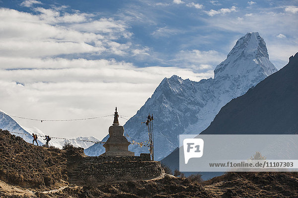 Trekkers near a chorten in the Everest region with the peak of Ama Dablam in the distance  Himalayas  Nepal  Asia