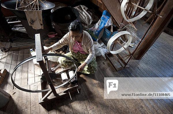 Woman spinning silk thread on a spinning wheel with bicycle wheel  Ko Than hlaing Weaving  Inpawkhan  Inle Lake  Shan state  Myanmar (Burma)  Asia