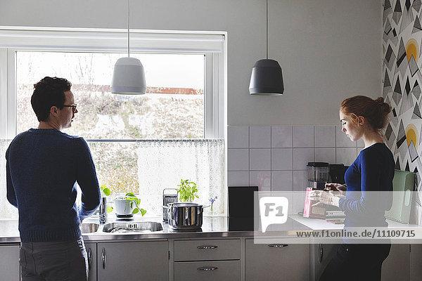Mann wäscht Geschirr  während Frau in der Küche kocht.