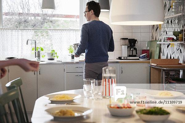 Essen auf dem Tisch gegen den Mann  der zu Hause an der Küchenzeile steht.