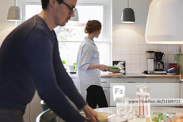 Mann arrangiert den Esstisch  während die Frau das Essen in der Küche zubereitet.