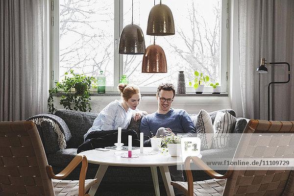Paar  das im Smartphone schaut  während es zu Hause auf dem Sofa sitzt.