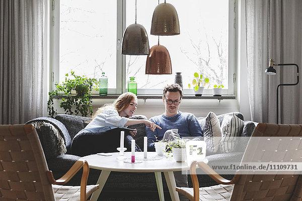 Paare  die zu Hause auf dem Sofa sitzen und Technologien nutzen