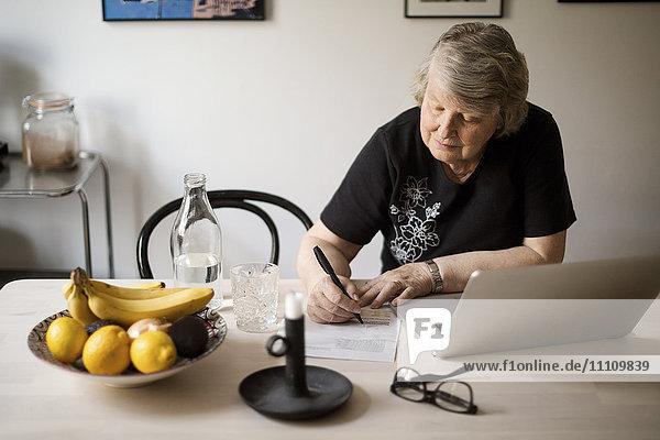 Seniorenfrau  die nach Rechnungen sucht  während sie den Laptop am Tisch benutzt.