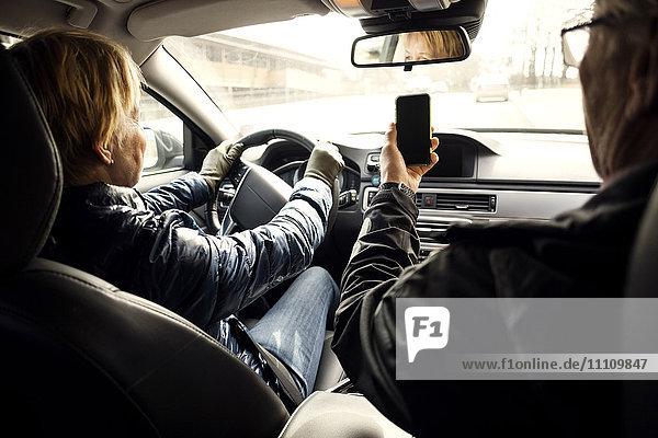 Senior Frau  die Auto fährt  während sie von Mann zu Mann sitzt und Selfie über Smartphone nimmt.