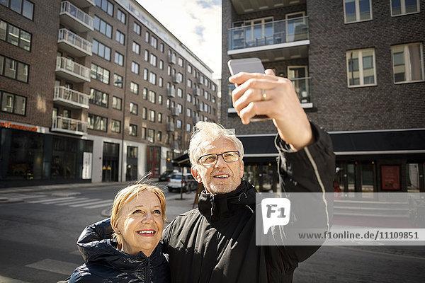 Senior Paar nimmt Selfie durch Smartphone  während er in der Stadt steht.