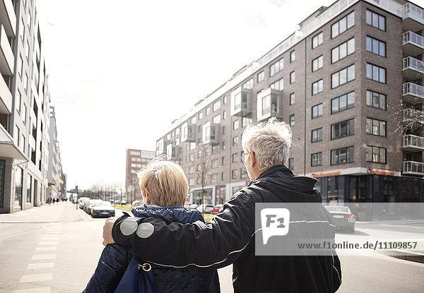 Rückansicht des Seniorenpaares  das auf der Stadtstraße gegen den klaren Himmel geht.