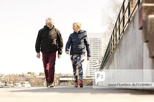 Seniorenpaar in Sportbekleidung beim Gehen auf dem Bürgersteig gegen den klaren Himmel