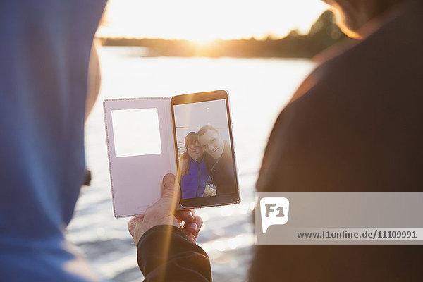 Rückansicht von Mann und Junge beim Betrachten des Fotos im Smartphone gegen den See