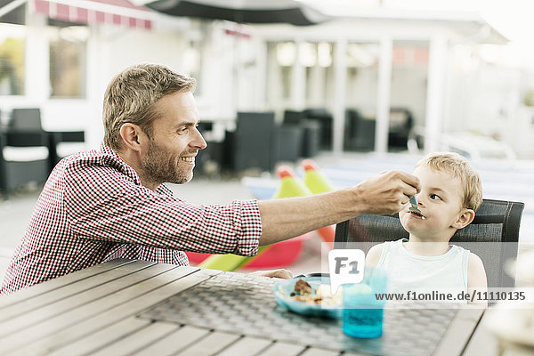 Smiling father feeding son while sitting at restaurant