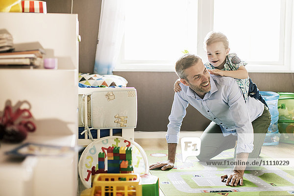 Junge reitet auf Vaters Rücken  während er zu Hause spielt.