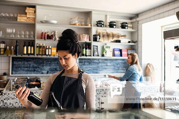 Zuverlässige Frau beim Prüfen von Flaschen  während die Kollegin im Hintergrund am Verkaufsdisplay steht.