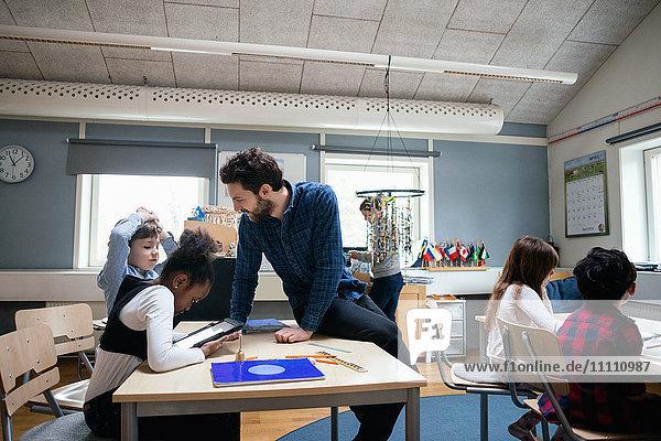 Männlicher Lehrer sitzt auf dem Schreibtisch und erklärt den Schülern die Verwendung des digitalen Tabletts im Klassenzimmer.