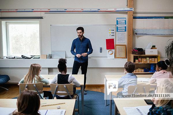 Confident teacher explaining students in classroom at school