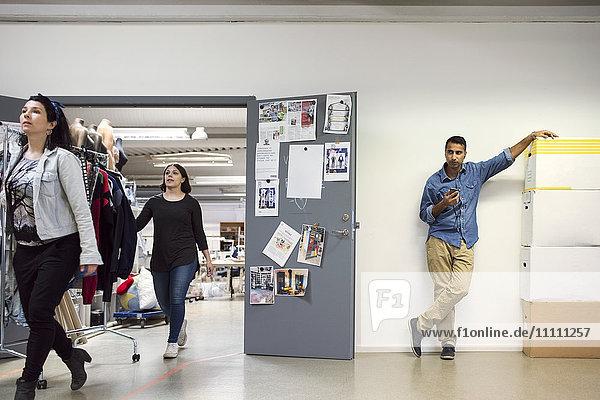 Freiwillige  die mit einem Kleiderständer von Mann zu Mann gehen  indem sie das Telefon gegen die Wand benutzen.