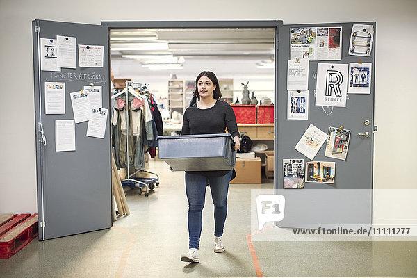 Frau  die eine Kiste trägt  während sie aus dem Eingang der Werkstatt geht.