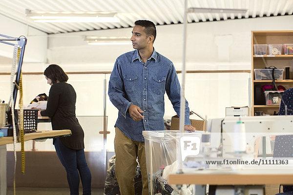 Mann steht neben dem Plastikbehälter  während er in der Werkstatt arbeitet.