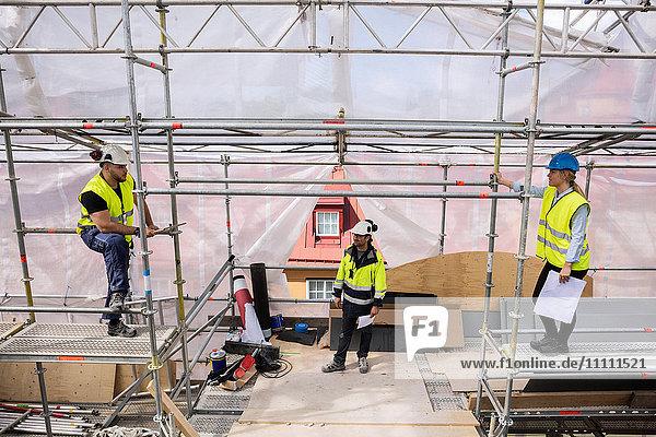 Hoher Blickwinkel auf die Mitarbeiter,  die auf der Baustelle dem Manager zuhören.
