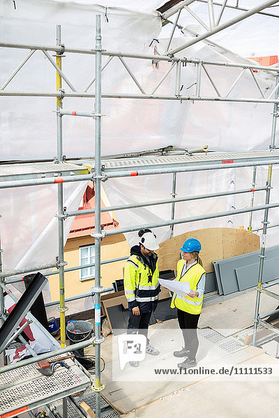 High angle view of female and male managers planning at construction site