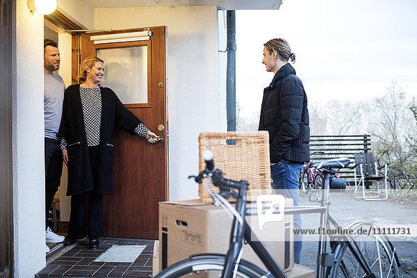Glückliche Eltern schauen auf den Sohn  der vor dem neuen Haus an Kartons und Fahrrädern steht.
