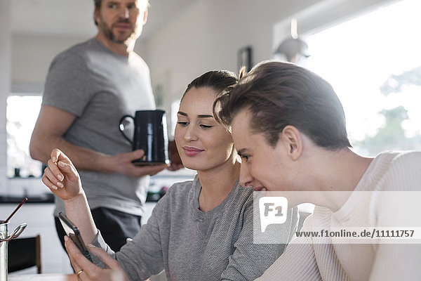 Geschwister mit Smartphone in der Küche  während der Vater einen Krug hält.