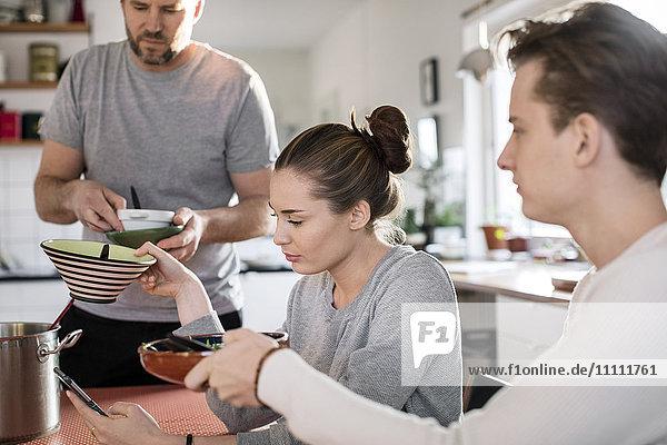 Bruder und Schwester geben dem Vater in der Küche Schalen.