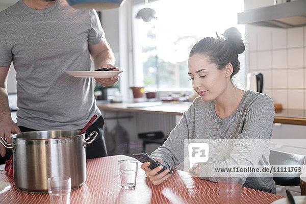 Mittelteil des Vaters  der die Platte hält  während die Tochter das Smartphone am Esstisch in der Küche benutzt.