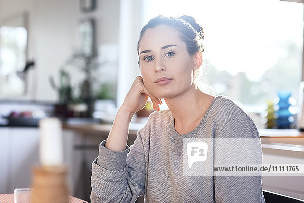 Portrait of confident woman sitting in kitchen at new home