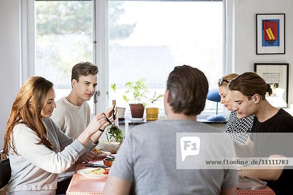 Familie beim Essen am Esstisch im neuen Haus